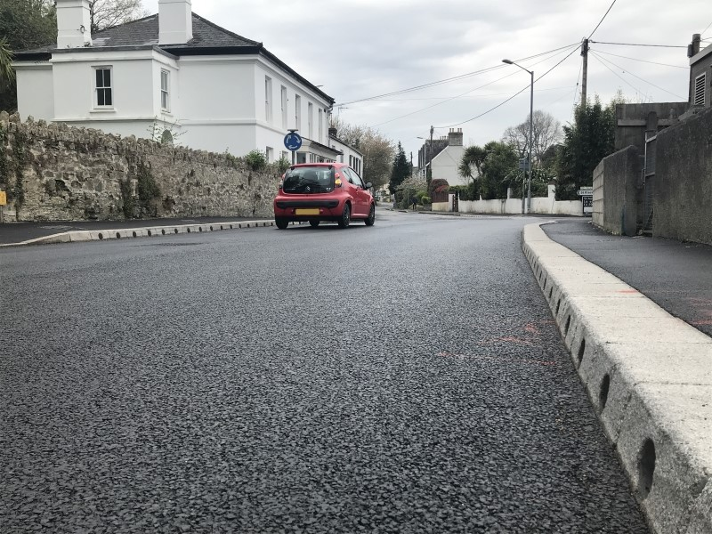 Car on road with kerbstones that have drainage holes